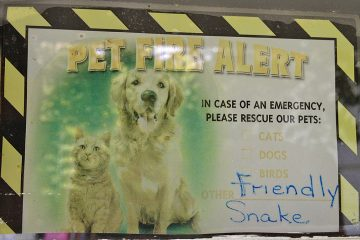A sign on the front door of Snakey's house lets emergency workers know that the boa constrictor is not a threat. (Zack Seward/WHYY)