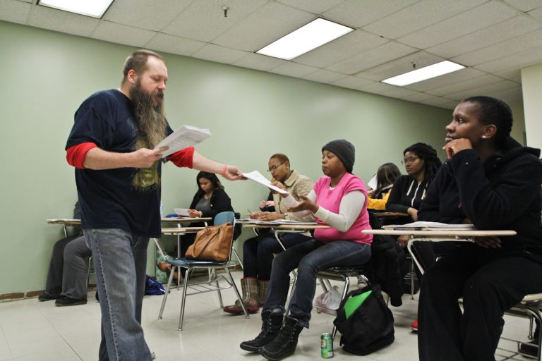 Dr. Rick Frei, associate professor of psychology at Community College of Philadelphia, hands out sample surveys to students who will collect data on  attitudes toward snitching. (Kimberly Paynter/WHYY)