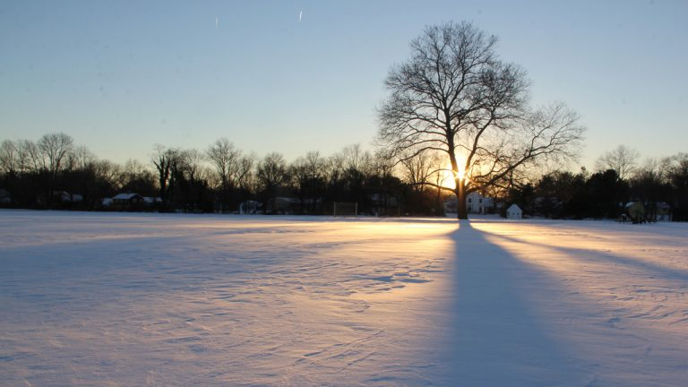 The sun sets over an unbroken field of snow. (Emma Lee/for NewsWorks, file)