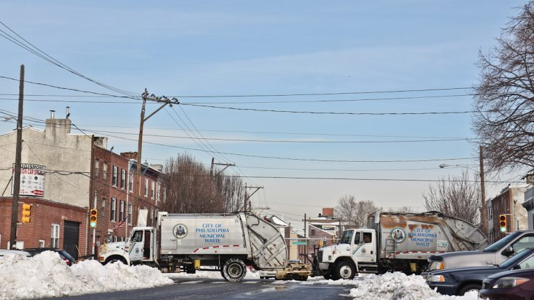 Garbage trucks with plows attached are still cleaning up South Philadelphia Monday morning. (Kimberly Paynter/WHYY)