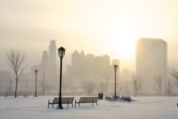 The Philadelphia skyline is faintly seen in the distance from Drexel Park due to high winds blowing fallen snow. (Nathaniel Hamilton/for NewsWorks)
