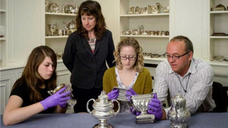 Senior Objects Conservator Bruno Pouliot (far right) and Curator of Decorative Arts Ann Wagner (standing) examine coatings