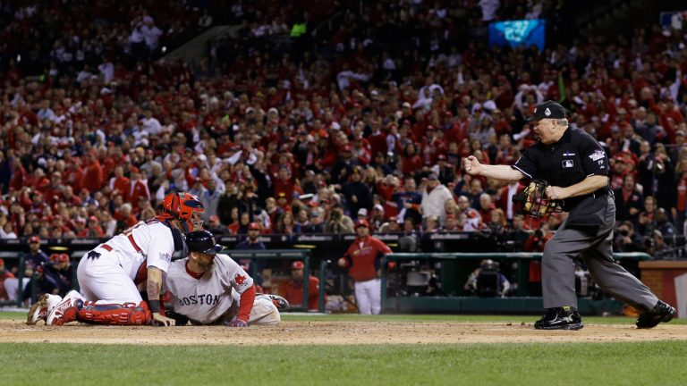 Home plate umpire Bill Miller makes the call as Boston Red Sox David Ross tags out St. Louis Cardinals catcher Yadier Molina as he tries to score from second on a single by Jacoby Ellsbury during the seventh inning of Game 5 of baseball's World Series Monday
