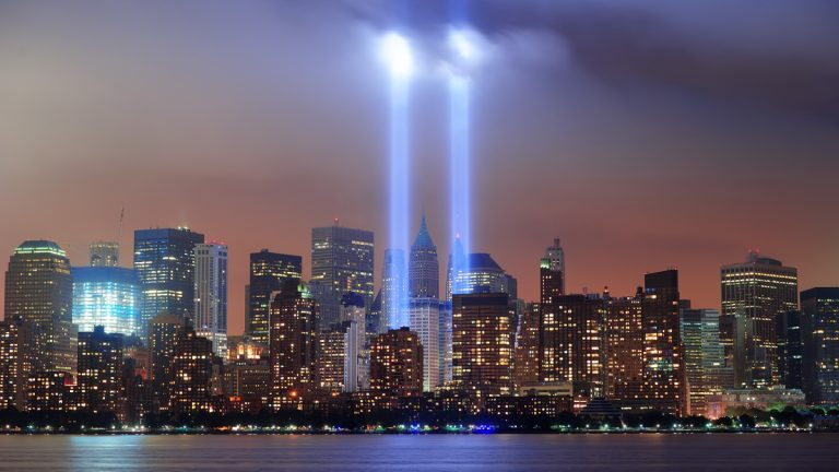 """New York City Manhattan downtown skyline at night from Liberty Park with light beams in memory of September 11 viewed from New Jersey waterfront.(<a href=""""http://www.shutterstock.com/pic-145527118/stock-photo-new-york-city-manhattan-downtown-skyline-at-night-from-liberty-park-with-light-beams-in-memory-of.html?src=e_0Wc42c4NifpEmhvxkQOQ-1-6"""">Photo</a> via ShutterStock)"""