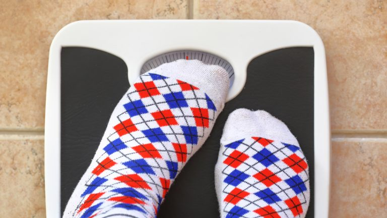 """(<a href=""""http://www.shutterstock.com/pic-258362069/stock-photo-woman-s-feet-on-bathroom-scale-diet-concept.html?src=zMLrpY4xAqAALCYuyLfeng-1-8"""">Photo</a> via ShutterStock)"""