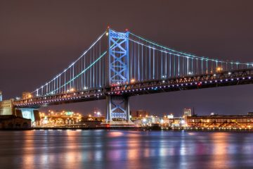 The Ben Franklin Bridge illuminated over the Delaware River. (Photo via Shutterstock)