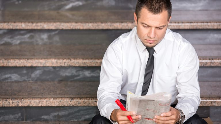 """(<a href=""""http://www.shutterstock.com/pic-226044718/stock-photo-young-unemployed-man-is-looking-for-a-job-in-the-newspaper-sitting-on-the-stairs.html?src=r94XmR_v4YsYw6RXkZnTww-1-2"""
