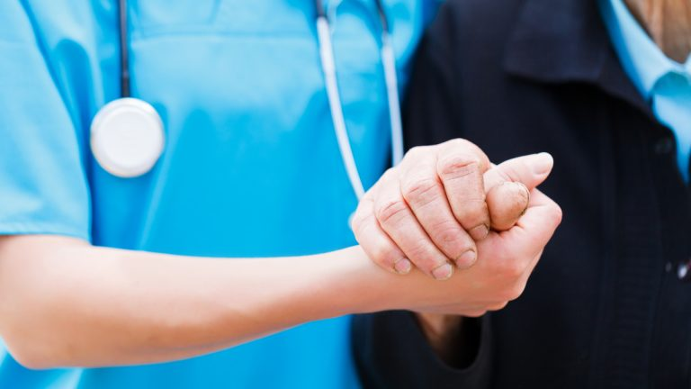 "(<a href=""http://www.shutterstock.com/pic-140404582/stock-photo-caring-nurse-or-doctor-holding-elderly-lady-s-hand-with-care.html?src=GnTfmErksevvrgEh3ib39A-1-1"">Photo</a> via ShutterStock)"