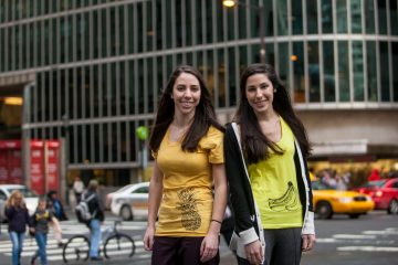 Twins Rachel and Sarah Stanton are shown wearing two of their Fruitstrology shirts. (Brad Larrison/for NewsWorks)