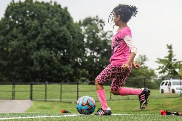 A camper attempts to make a goal at Starfinder Soccer camp on the astroturf field in Hunting Park. (Kimberly Painter/WHYY)