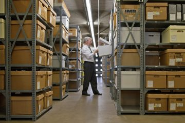 David Carmichael, director of Pennsylvania State Archives, looks though one of many boxes that holds permanent pension records in Harrisburg, Pa. (Lindsay Lazarski/WHYY)