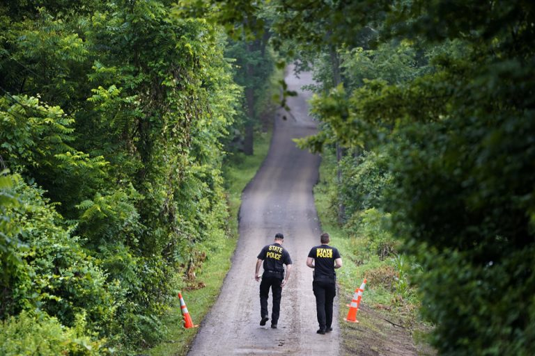 Pennsylvania State Police officers walk up a driveway, Friday, July 14, 2017, in Solebury, Pa. (Matt Rourke/AP Photo)