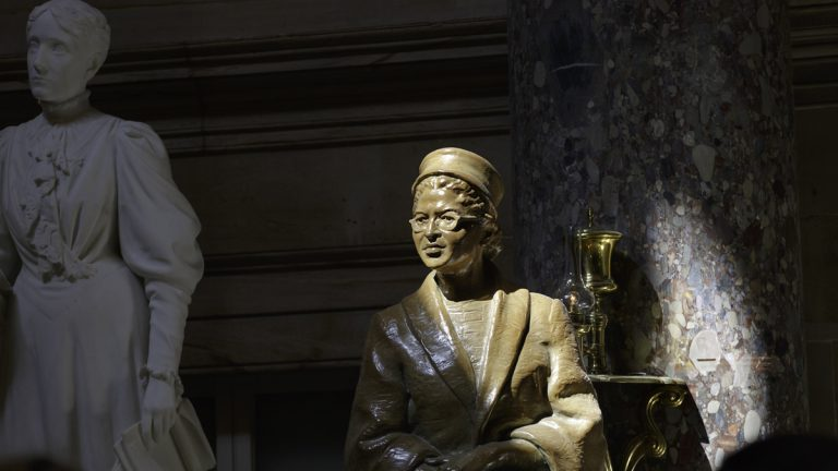 A bronze statue of civil rights icon Rosa Parks is illuminated in a beam of light in Statuary Hall at the U.S. Capitol. A marble statue of temperance pioneer Frances E. Willard is shown in the background. (AP Photo/J. Scott Applewhite, file)