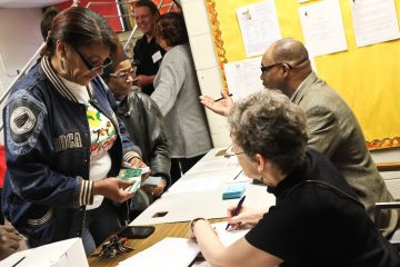 Fatima Byrd has a son at Steel and presents identification to be able to vote to keep the school public. (Kimberly Paynter/WHYY)