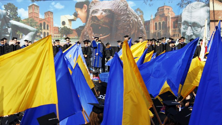 UCLA student-athletes and scholars carry 99 flags at a commencement ceremony in 2010. (AP Photo/Reed Saxon