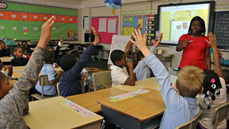 Second-graders raise their hands at Chester Arthur Elementary School. (Emma Lee/WHYY