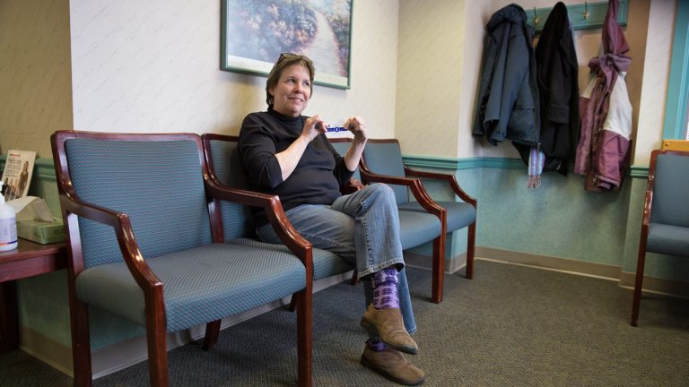 Suzanne Cloud, executive director of Jazz Bridge is on a mission to get musicians to sign up for Affordable Care Act.  She shows off her new health insurance cards as she waits to be seen by her doctor at Cooper Medical Services in Cherry Hill, N.J. (Lindsay Lazarski/WHYY)