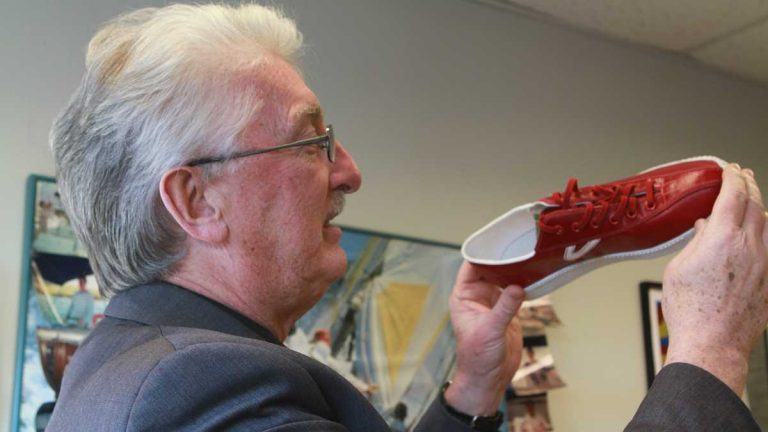 Richard Wool holding a sneaker made of