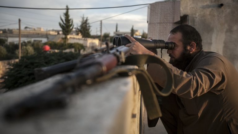 A Syrian opposition fighter watches over as heavy fighting sparks out in the neighboring village of Kafr Nabuda in the Idlib province countryside, Syria, Thursday, Sept. 19, 2013.  (AP Photo)