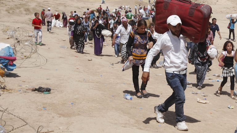 Syrian refugees cross into Iraq at the Peshkhabour border point in Dahuk, 260 miles northwest of Baghdad on Tuesday, Aug. 20. (AP Photo/Hadi Mizban)