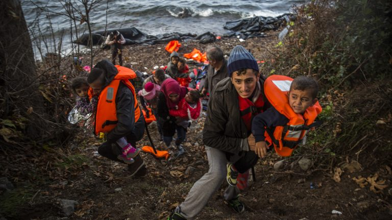 Syrian refugees climb up to a field after arriving from Turkey at the Greek island of Lesbos on an overcrowded dinghy, Tuesday, Oct. 27, 2015. Greece's government says it is preparing a rent-assistance program to cope with a growing number of refugees, who face the oncoming winter and mounting resistance in Europe. (AP Photo/Santi Palacios)