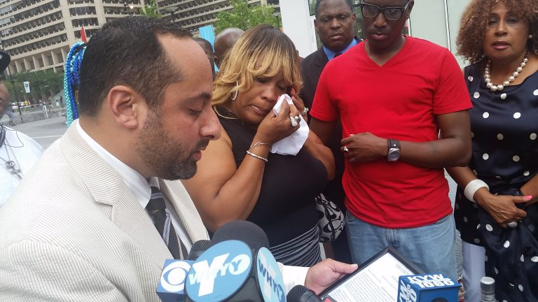 As family attorney Brian Mildenbergspeaks, Brandon Tate-Brown's mother wipes tears from her eyes at a City Hall press conference. (Tom MacDonald/WHYY)