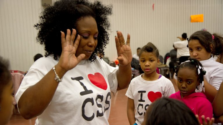 Camden Sophisticated Sisters' leader Tawanda Jones gives high fives to members of the step team.  (Lindsay Lazarski/WHYY, file)