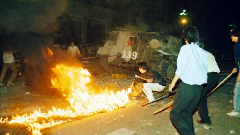 Student protesters are shown putting a barricade in front of a burning armored personnel carrier that rammed through student lines, June 4, 1989. Many were injured and killed during an army attack on pro-democracy demonstrators in Beijing's Tienanmen Square. (AP Photo, file)