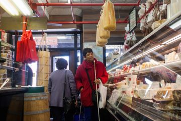 Denice Brown visits a cheese and meat shop during a Philly Touch Tour of the Italian Market. (Brad Larrison/for NewsWorks)