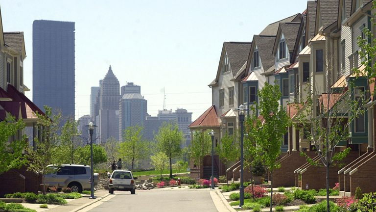 The Pittsburgh skyline rises on the horizon behind townhouses