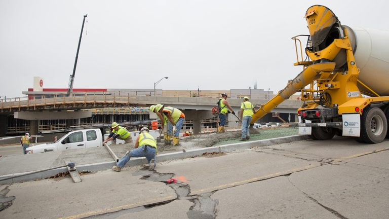 Construction workers pour concrete near the East Liberty transit station in Pittsburgh, Pa. (Lindsay Lazarski/WHYY)