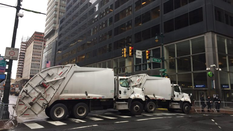 Trash trucks are shown blocking Market Street outside of the GOP congressional retreat where President Trump will visit. (Dana DiFilippo/WHYY)