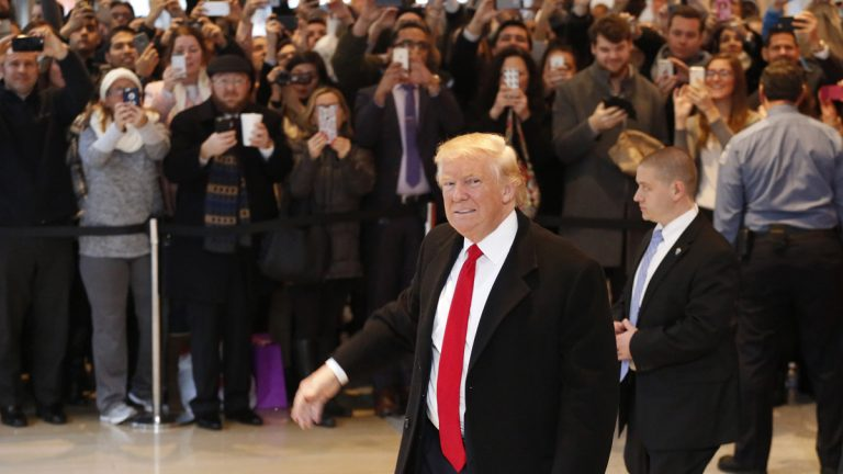 President-elect Donald Trump walks past a crowd as he leaves the New York Times building following a meeting