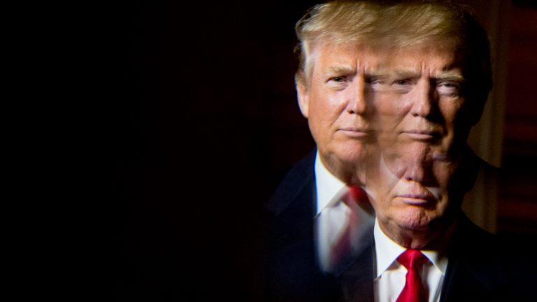 Republican presidential candidate Donald Trump, seen in reflection, poses for a portrait following an interview with the Associated Press at the Trump National Golf Club in Sterling, Va., Wednesday, Dec. 2, 2015. (AP Photo/Andrew Harnik)