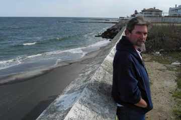 Tim Dillingham, director of the American Littoral Society, leans against a wall on a dead-end street in Deal, N.J. He'd like local officials to tear down the wall and build a set of stairs to the beach below, in order to improve the public's access to the water (Tracey Samuelson/WHYY)