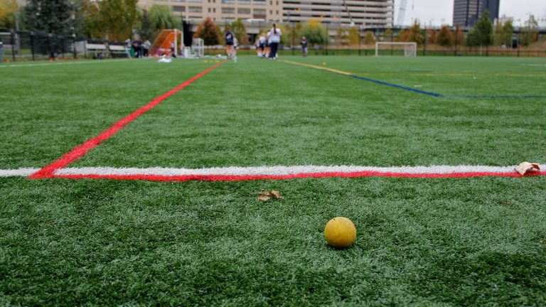 A lacrosse team practices on the artificial turf at Penn Park in Philadelphia. (Emma Lee/WHYY)