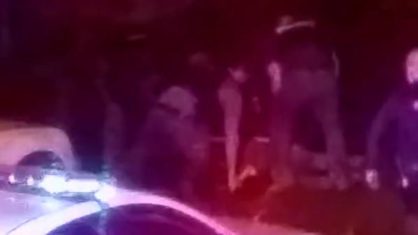 A screenshot from a phone video show police gathered around Tyree Carroll. (Courtesy of Tyree Carroll Family)