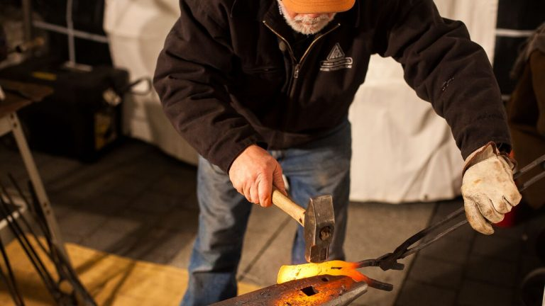 Blacksmith Mike Martin, who founded the Colorado-based nonprofit RawTools after the 2012 Sandy Hook shooting, transforms a rifle into a farm tool Wednesday night. (Brad Larrison/ for NewsWorks)