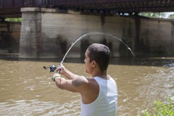 Jeremy Viejegas casts his line into the Schuylkill River in Reading. (Jessica Kourkounis/for WHYY)