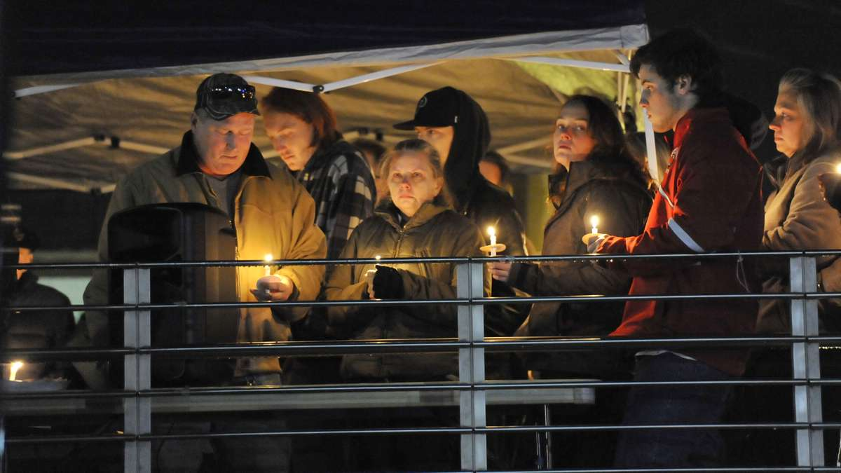 Shane Montgomery's parents, Karen and Kevin Montgomery (left) are joined by friends and family during a candlelight vigil held on the campus of West Chester University last week. (Jonathan Wilson/for NewsWorks)