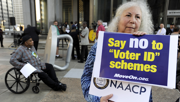 In this September 2012 photo, a protestor holds a sign during the NAACP voter ID rally to demonstrate the opposition of Pennsylvania's voter identification law, which requires each voter to show valid photo identification. (Michael Perez/AP Photo, file)