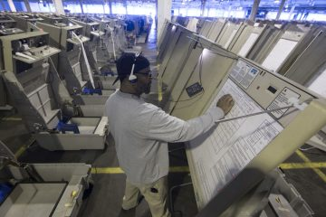 A technician works to prepare voting machines to be used in the upcoming presidential election