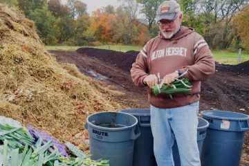 Scott Blunk sorts through additions to the compost at the W.B. Saul High School farm. (Neema Roshania Patel/WHYY)