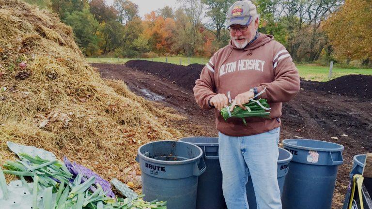Scott Blunk sorts through additions to the compost at the W.B. Saul High School farm. (Neema Roshania Patel/WHYY)
