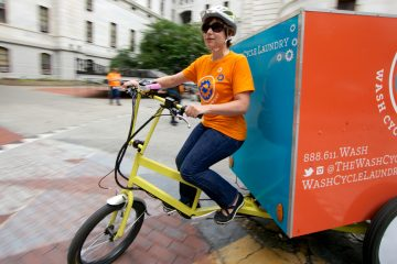 Andrea Adleman rides one of Wash Cycle Laundry's special delivery trikes. The company is expanding to Washington, D.C., its second market. (Nathaniel Hamilton/for NewsWorks)