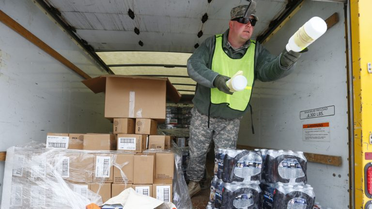 Michigan National Guard Staff Sgt. James Green hands out a water test kit to be distributed to residents