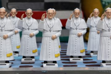 A window display at The Fabric Workshop (1214 Arch Street) features an array of waving Pope Francis statues. (Emma Lee/WHYY)