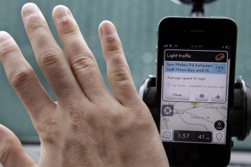 A driver waves his hand over a traffic and navigation app called Waze on his Apple iPhone. (AP Photo/Paul Sakuma