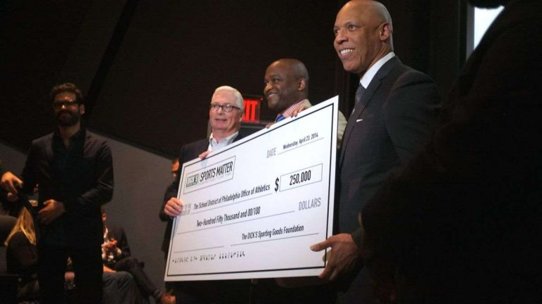 Edward Stack, CEO of DICK's Sporting Goods, presents Superintendent William Hite and MLK Principal William C. Wade with a check for $250,000. (Brad Larrison/for NewsWorks)
