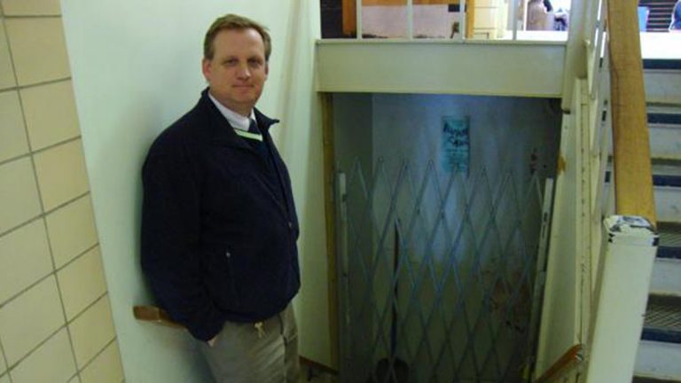 State High dean of students, Chris Weakland, stands next to the entrance to storage space under the auditorium stage. It's gated because of flooding and mold.(Emily Reddy for WPSU)